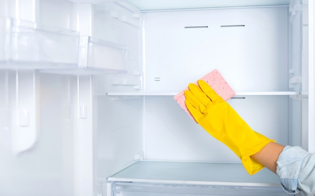 A woman's hand in a yellow rubber protective glove and a pink sponge washes and cleans the refrigerator shelves. cleaning service, housewife, routine housework. glass cleaner.