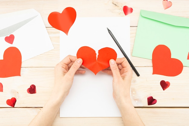 Woman's hands are holding a torn paper red heart. loss of love, message, letter