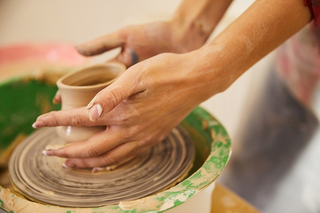 Woman's hands are moulding a vase on a circle