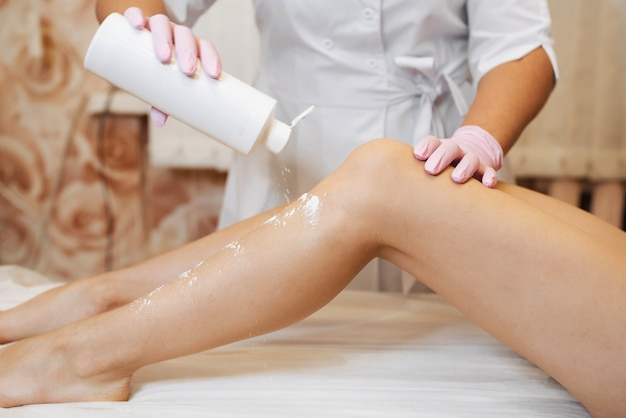 Woman's hands of a beautician preparing a slender female legs to the procedure of sugar hair removal