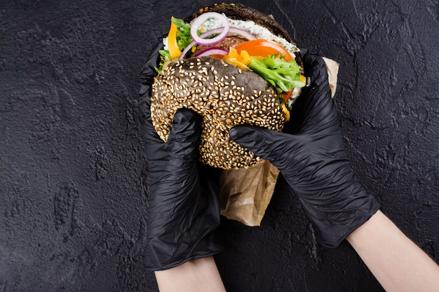 Woman's hands in black rubber gloves are holding juicy black bun burger