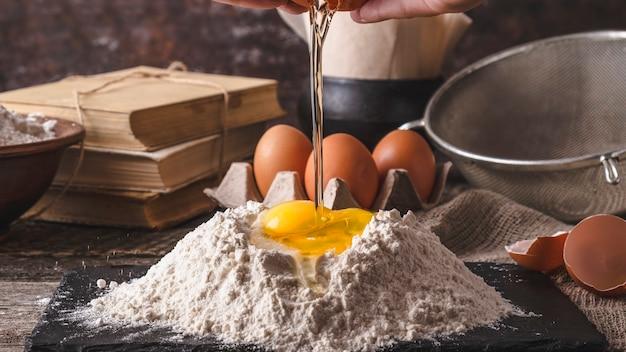 Руки женщины разбивают яйцо в муку. тонированное фото
