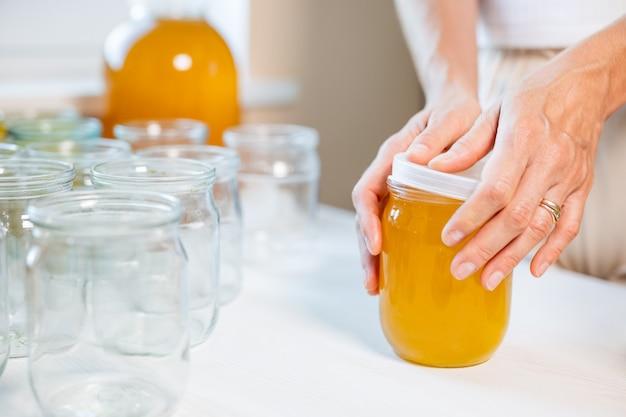女性の手は、白いテーブルの上に立っている蜂蜜の瓶の蓋を閉じ、スプーンで受け皿の横にあります