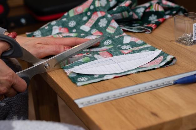 Крупным планом женские руки режут ножницами красную ткань и делают украшения.