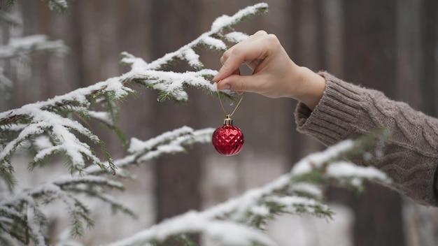 야외 크리스마스 트리를 장식하는 여자의 손 근접 촬영
