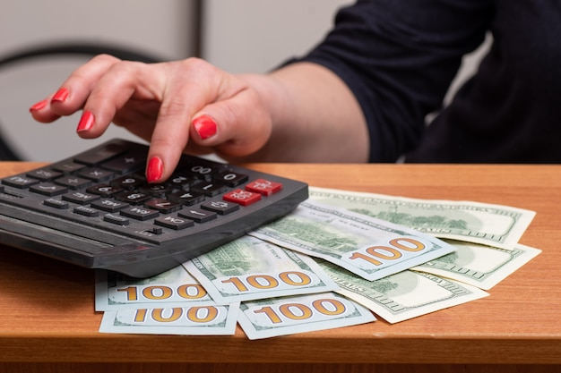 Woman's hands, consider on the calculator hundred dollar bills over the table.