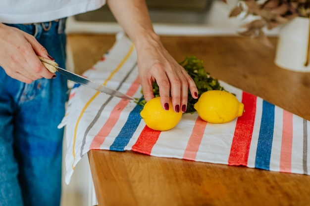 Woman's hands cutting yellow lemons on a colourful kitchen towel