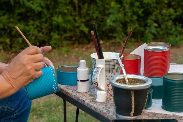 Женские руки украшают металлические контейнеры разноцветной краской. руки женщины украшают металлические контейнеры разноцветной краской.