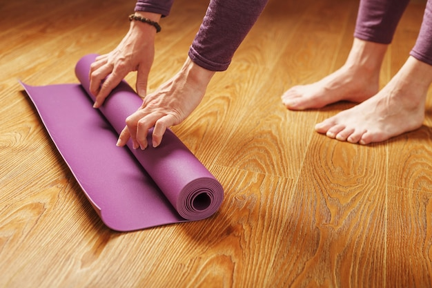 A woman's hands fold a lilac yoga or fitness mat after a workout at home in the living room. healthy lifestyle, asana and meditation practices