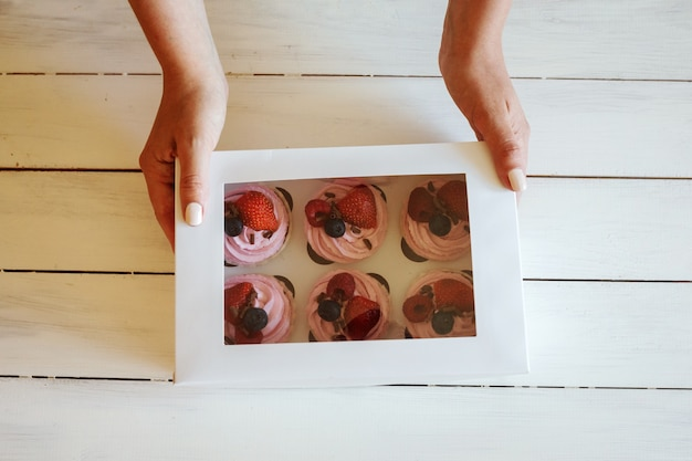 Женские руки держат коробку с кремовыми кексами со свежими ягодами. доставка десертов. белый