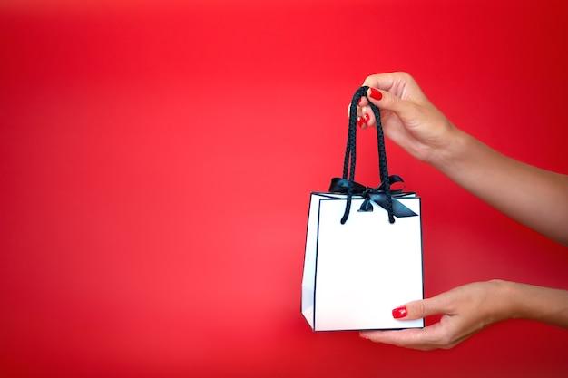 Женские руки держат белый подарочный пакет