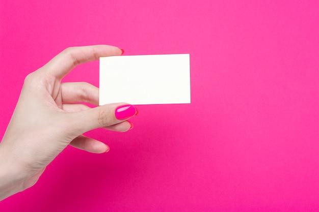 女性の手がピンクの紙に分離された空白の名刺を保持します。