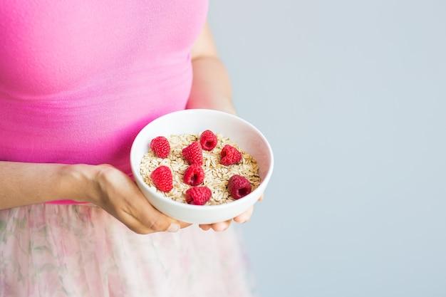 Женские руки держат в миске здоровый и натуральный завтрак, овсянку и малину.