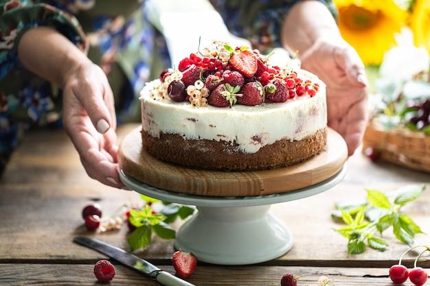 女性の手は自家製ベリーチーズケーキ、セレクティブフォーカスを保持します。横型