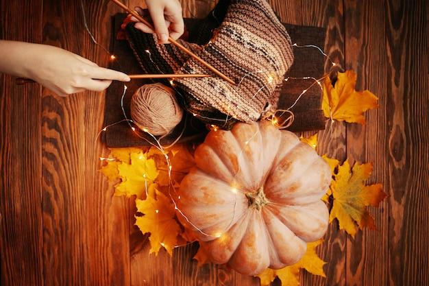 色とりどりの糸で作られた暖かいスカーフ、女性の手が編み針を握る