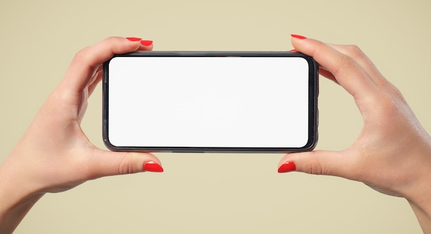 A woman's hands hold a smartphone with a blank white screen horizontally. on a cream background.