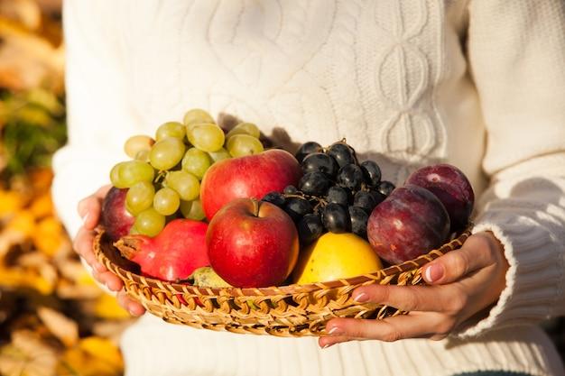 新鮮な果物のバスケットを持っている女性の手。閉じる