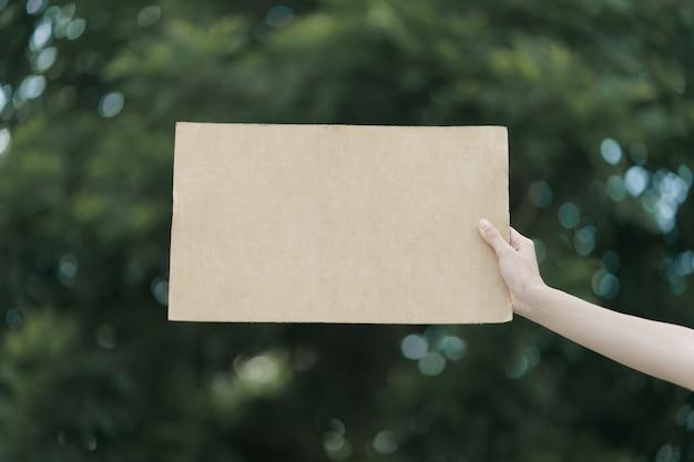 テキストに抗議するために空白のプラカードを持っている女性の手。