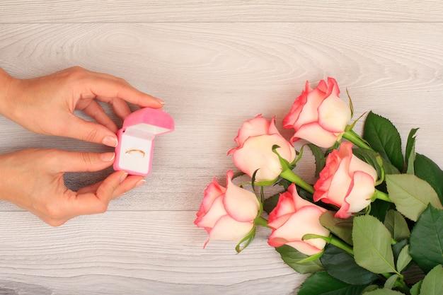 美しいバラと灰色の木製の背景の上に金の指輪のボックスを保持している女性の手。休日に贈り物をするという概念。上面図。