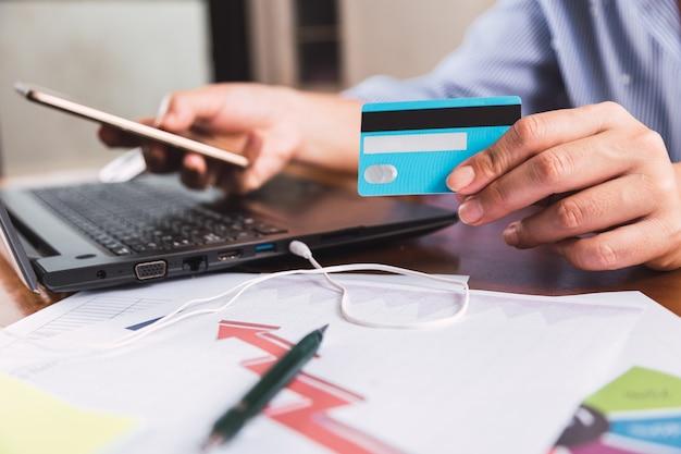 クレジットカードを持ってスマートフォンを使用している女性の手。