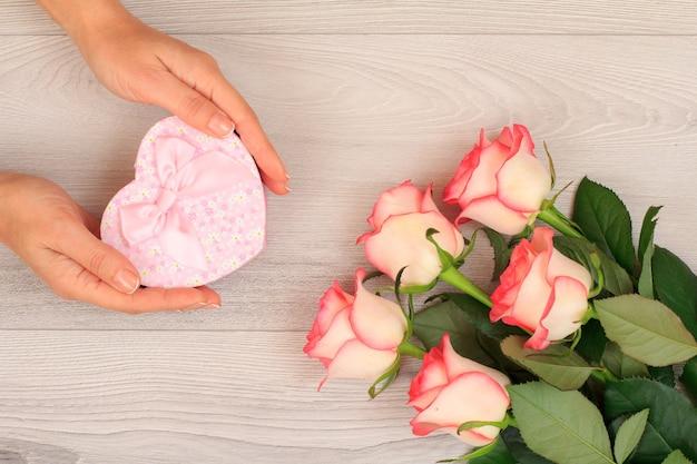 아름다운 장미가 있는 회색 나무 배경 위에 하트 모양의 선물 상자를 들고 있는 여성의 손. 휴일에 선물을 주는 개념. 평면도.