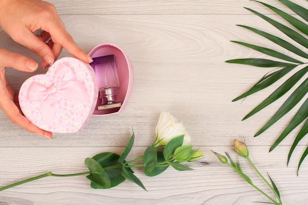 아름다운 꽃과 녹색 잎이 있는 회색 나무 배경 위에 향수 한 병을 넣은 하트 모양의 선물 상자를 들고 있는 여성의 손. 휴일에 선물을 주는 개념. 평면도.