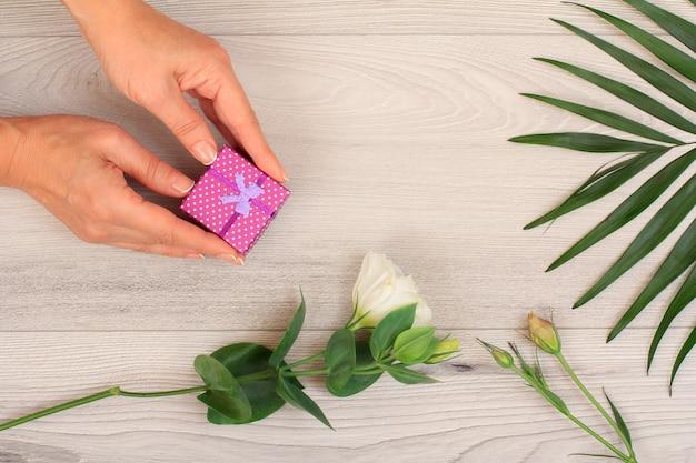 아름다운 꽃과 녹색 잎이 있는 회색 나무 배경에 선물 상자를 들고 있는 여성의 손. 휴일이나 생일에 선물을 주는 개념. 평면도.