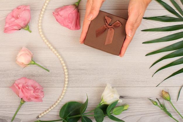 美しい花と緑の葉と灰色の木製の背景にギフトボックスを保持している女性の手。休日に贈り物をするという概念。上面図。