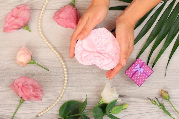 아름다운 꽃과 녹색 잎이 있는 회색 나무 배경에 선물 상자를 들고 있는 여성의 손. 발렌타인 데이 또는 생일에 선물을 주는 개념. 평면도.