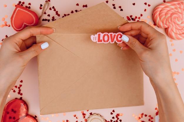 장미 배경에 공예 봉투에 편지를 들고 여자의 손. 그리고 봉투에 사랑이라는 단어를 넣습니다. 발렌타인 데이 개념.