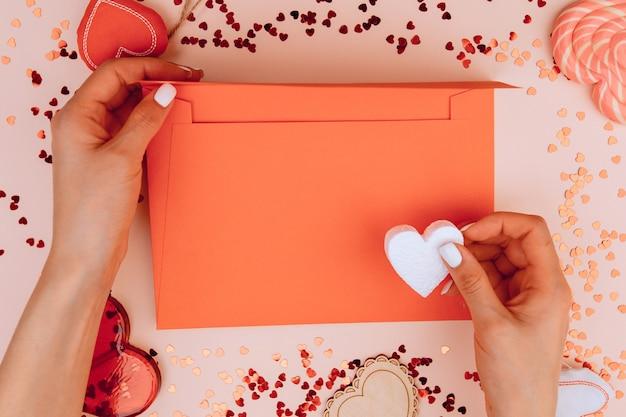 장미 배경에 공예 봉투에 편지를 들고 여자의 손. 발렌타인 데이. 텍스트를위한 공간.