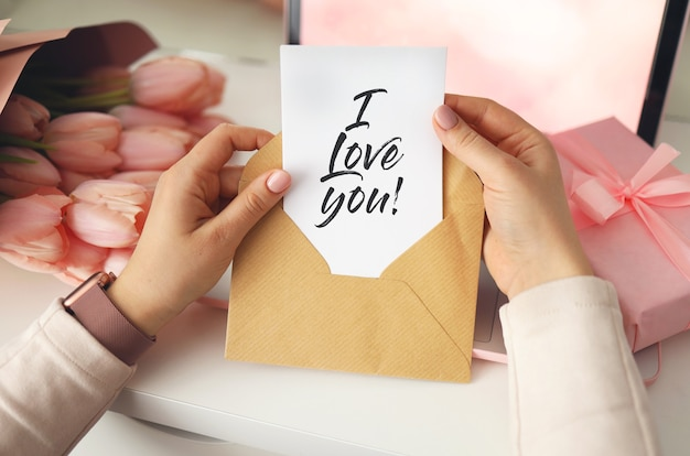クラフト封筒に手紙を持っている女性の手。ピンクの背景、バレンタインデーのコンセプト。背景にチューリップの花とピンクのギフトボックス。レディースホームデスク。私はあなたのフレーズが大好きです。
