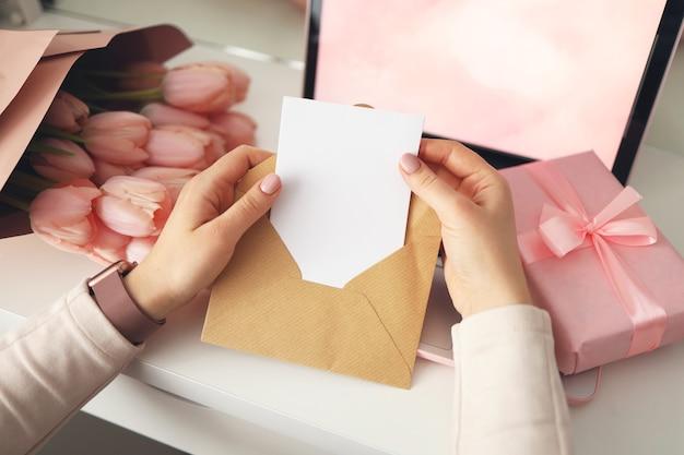 クラフト封筒に手紙を持っている女性の手。ピンクの背景、バレンタインデーのコンセプト。背景にチューリップの花とピンクのギフトボックス。レディースホームデスク。
