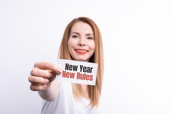 Руки женщины, держа записку с новым годом меня текстом.