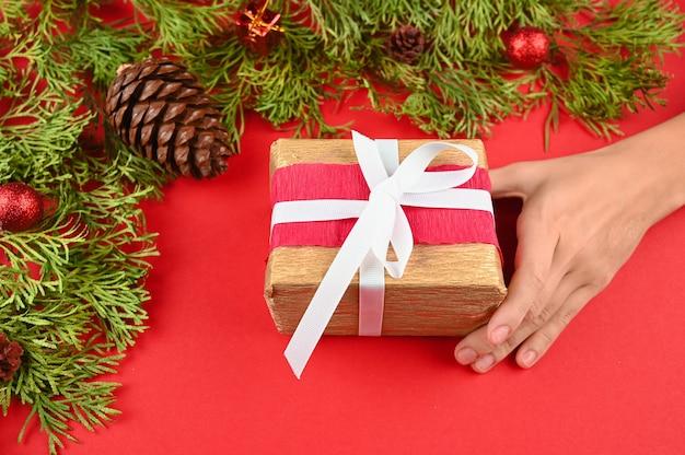 Женские руки, держа красный подарок