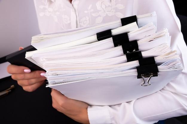 ドキュメントのスタックを保持している女性の手 Premium写真