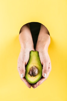 Woman's hands holding an avocado out of a black hole in a yellow paper wall.