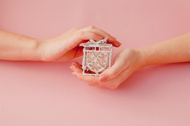 ピンクの背景、仮想通貨のシンボルのピンクのギフトボックスでビットコインを保持している女性の手。