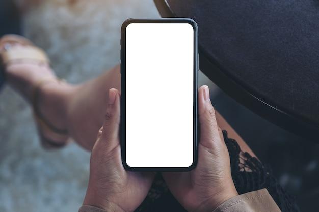 カフェに座っている間空白の白い画面で黒い携帯電話を保持している女性の手