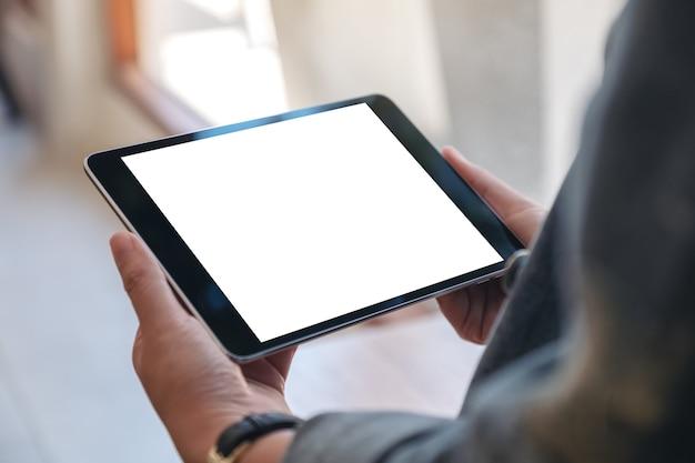 Женские руки держат черный планшетный пк с пустым экраном по горизонтали в кафе
