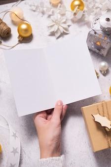 Женские руки, держа пустую карточку на белом фоне. рождественский зимний дизайн. макет, вид сверху