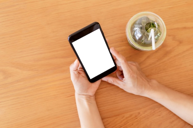 Woman's hands holding blank empty screen smartphone in cafe