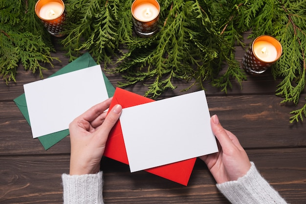 Woman's hands holding blank paper greeting or invitation card. chritsmas design.