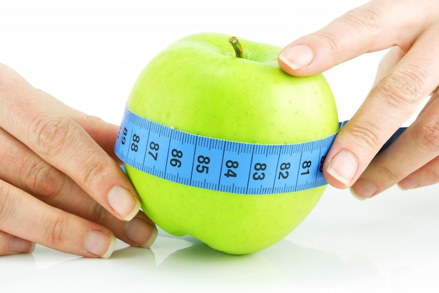 Woman's hands holding bright green apple and measuring tape isolated