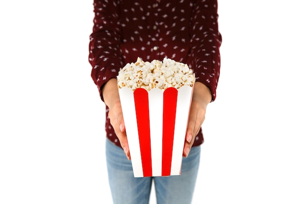 Le mani della donna che tengono secchio con popcorn su fondo bianco