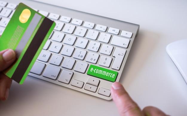オンラインショッピング、eコマース、お金を使う、バイヤー、消費者、テクノロジーのためにコンピューターを使用してクレジットカードを保持している女性の手