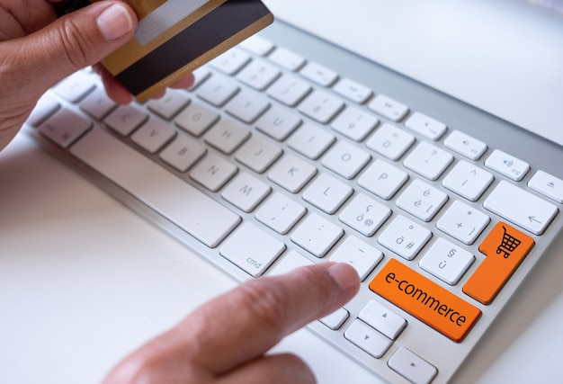 Woman's hands holding credit card using computer for online shopping, e-commerce, spending money, buyer, consumer, technology
