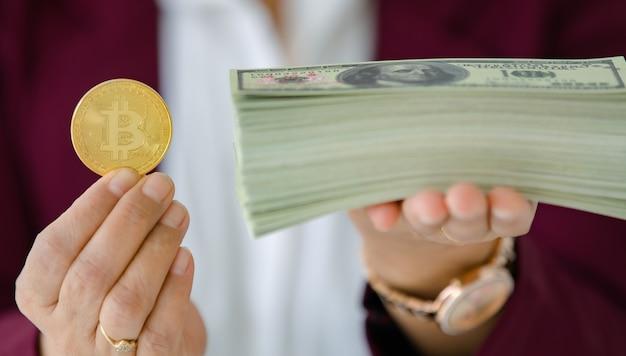 Женские руки, держа крипто монету и стопку денег банкнот и жест сравнения. концепция инвестиций в цифровые активы и олдскульные сокровища.