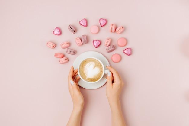 淡いピンクの背景にコーヒーのカップを保持している女性の手。フラットレイ、上面図