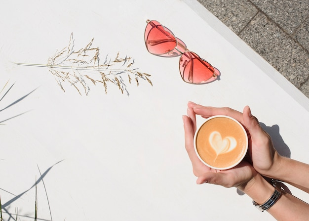 白い背景の上のコーヒーや紅茶のカップを保持している女性の手。トップビューポリスチレンコーヒーマグカップ。取り除く。広告コーヒー。